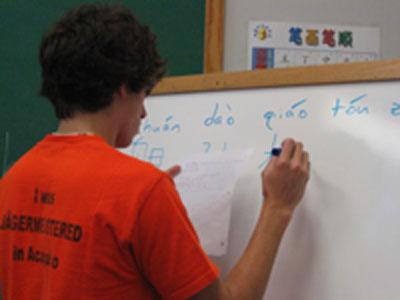 a male student writes on a whiteboard