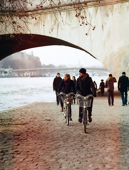 people riding bicycles along a riverbank