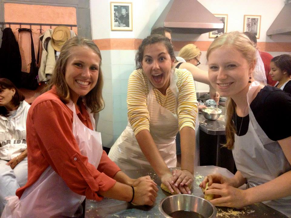 three students knead dough in a kitchen in Florence, Italy