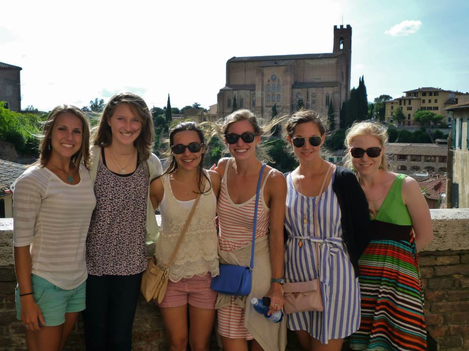 six UA students pose in front of a large building in Florence, Italy