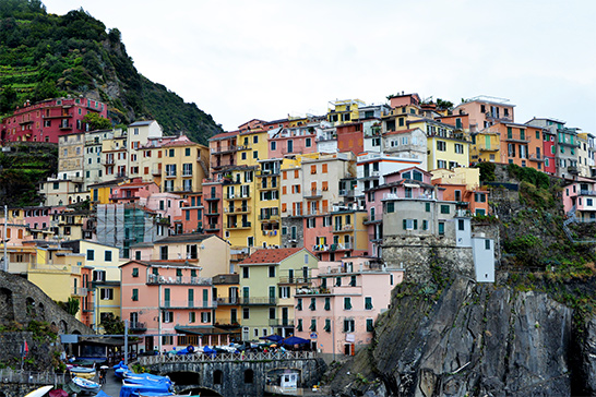 a cluster of pastel-colored buildings cling to a hillside