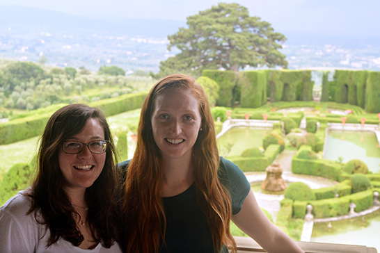 two students pose in front of the gardens at a monastery