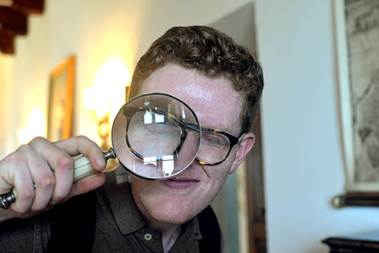 young man holding a magnifying glass in front of one eye