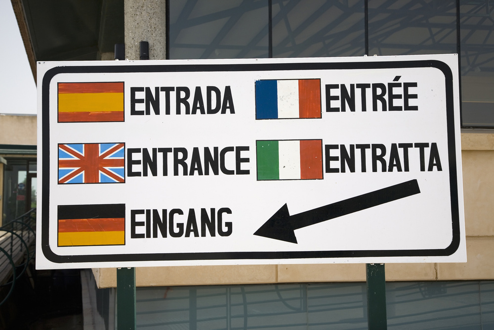"""a sign showing the word """"entrance"""" rendered in five related European languages"""