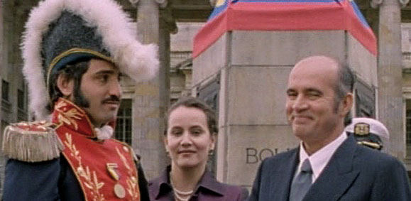 two men, one in ceremonial dress, and a woman converse outside a building