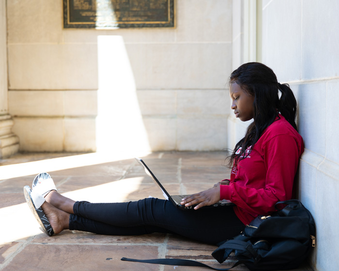 student studying on the steps of Gorgas Library