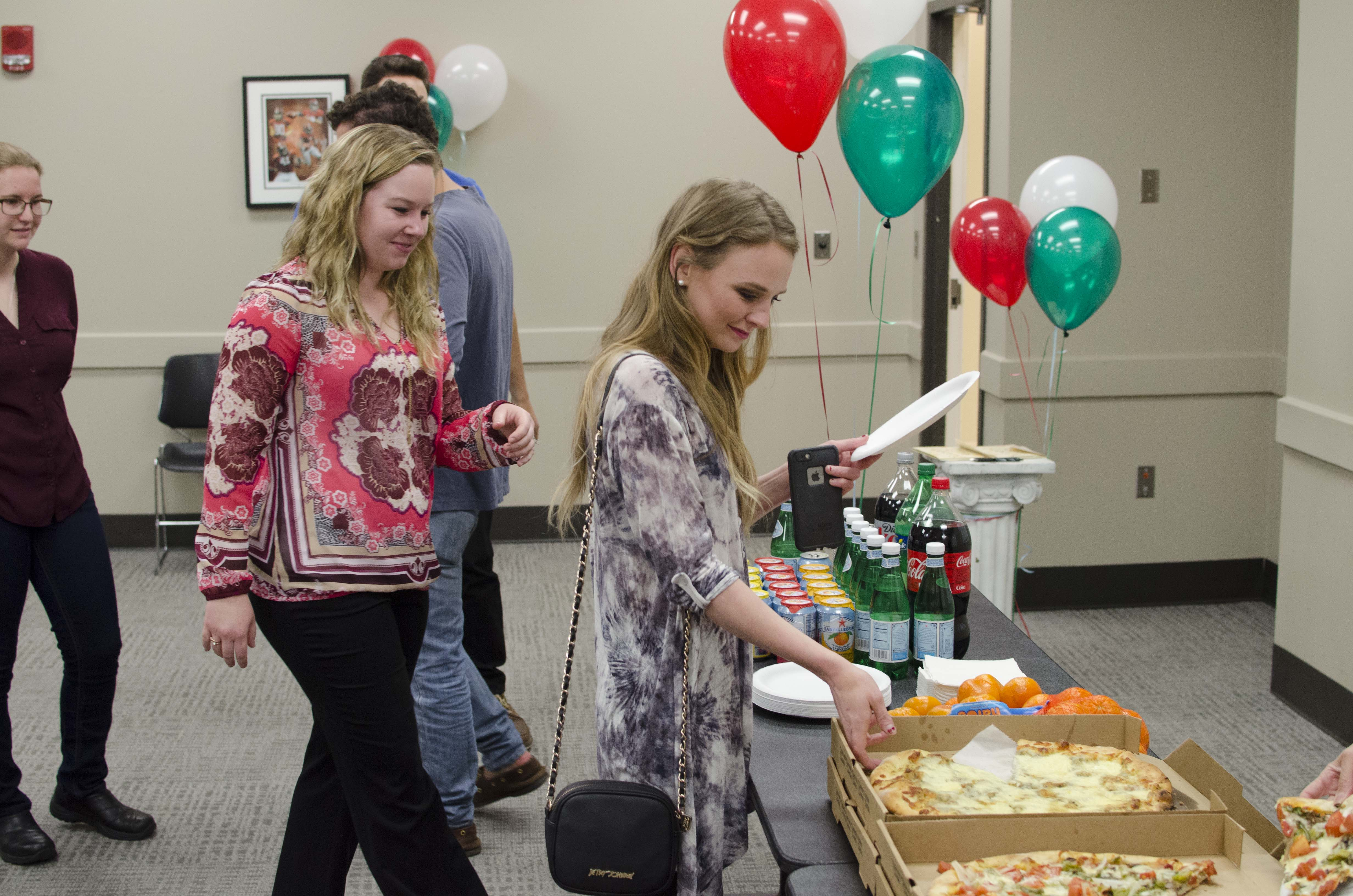 students help themselves to pizza at an Italian Club event